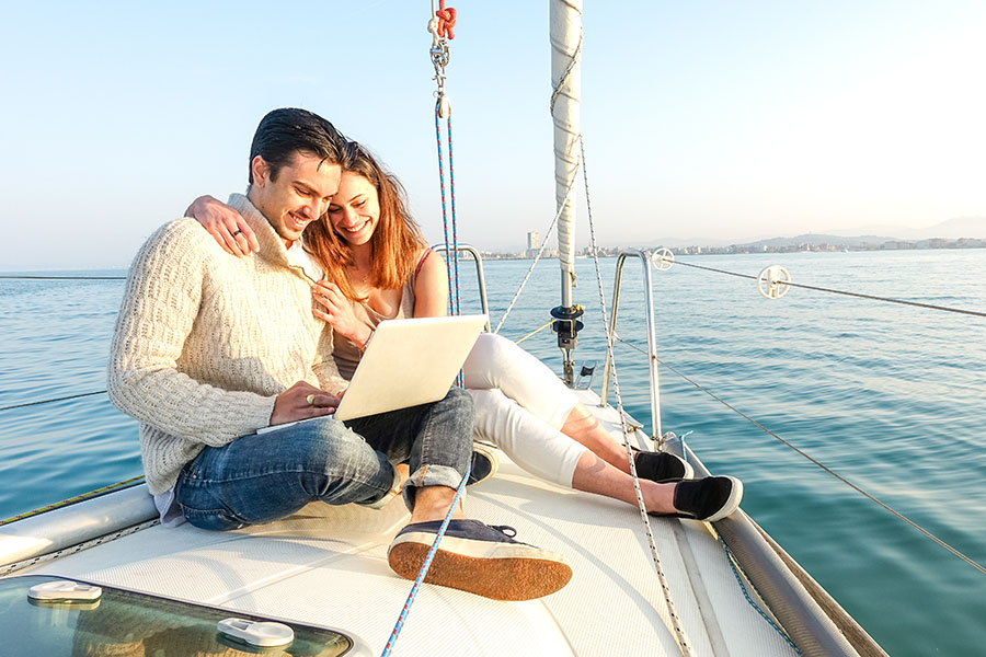 Client Center - Young Couple Sitting On Yacht At Sea Using Laptop