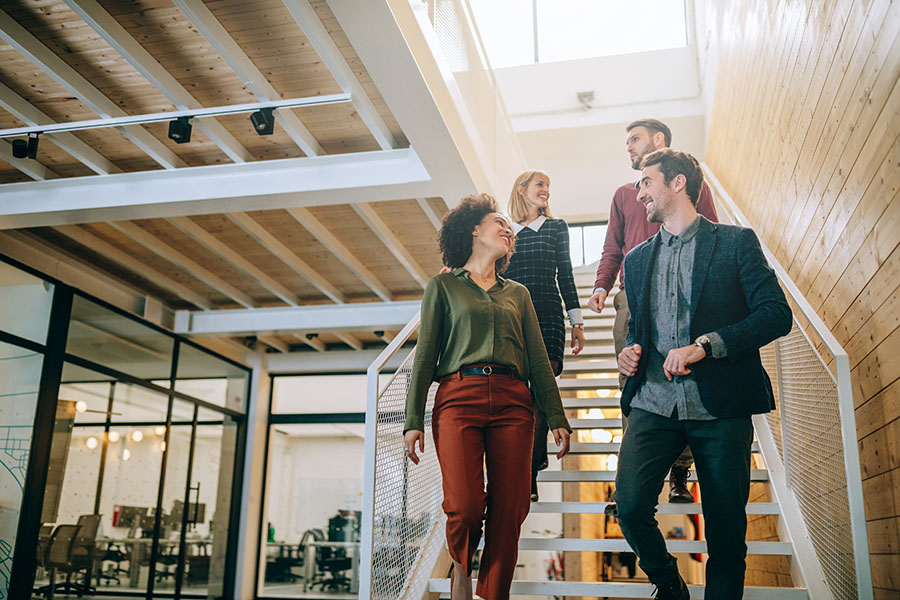 Employee Benefits - Group Of Employees Smiling While Walking Down Stairs In Modern Office