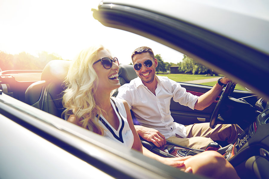 Personal Insurance - Smiling Couple Driving Together In Luxury Car